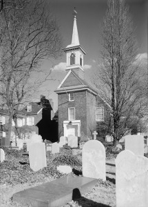 A black and white photograph of the front of a church, with a visible tower and graveyard stones in the foreground.