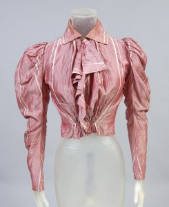 photograph of a dark rose shirtwaist blouse, displayed on a headless mannequin