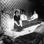 black and white photograph of two women and a man, standing center, posing near a large sewing table