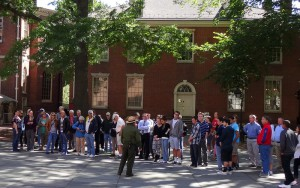 Color photo of a park service ranger speaking to tourists before they begin the Independence Hall tour.