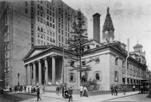 Photograph of the second US mint, from the exterior and from across the street, adjacent to the building. It is two stories high with a row of columns in the front