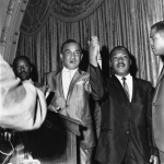 A black and white photo of NAACP leader Cecil B. Moore and Martin Luther King, Jr. holding hand together at a press conference