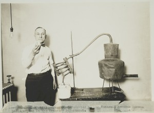 An Internal Revenue Service (IRS) agent scrutinizes the contents of a moonshine still during the Prohibition era.