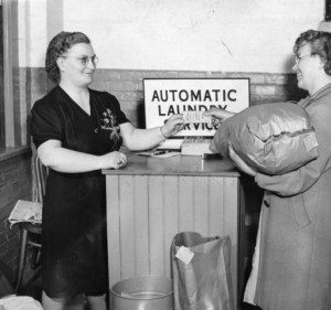 a photograph of two women using the automatic laundry service. the woman ont he left is taking a ticket from the woman on the right, who seems to be either picking up or returning her laundry