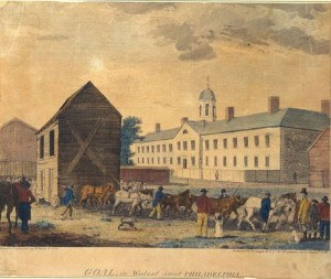 A color painting of the walnut street jail, a wide, rectangular building with a short steeple, which is placed in the background. A crowd of people and horses passes by in the foreground