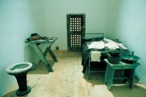 photograph of a solitary cell recreation. there is a twin bed to the right of the picture and a small night table at the foot of the bed. the left side of the room has small work table and a toilet. a door in the back of the cell leads to the work yard.