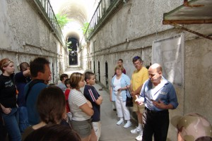a tour guide, to the right of the photo, leads a group of visitors through a cell block, while explainging the history of eastern state to them