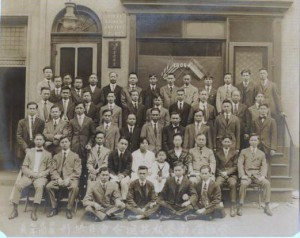 black and white photo of a group of about 45 men, two women, and a child seated in a pose in front of the First Chinese Baptist Church, Chinatown, Philadelphia. probably in the early 20th century.