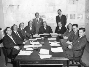 black and white photograph of eleven men in suits, nine sitting and two standing, around a conference table