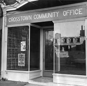photograph of the crosstown community office storefront. In the window's reflection, delapitated row homes are visible