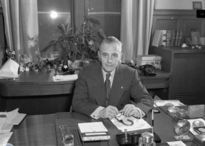 A black and white photograph of Richardson Dilworth seated at his desk