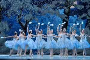 A color photograph of ballet dancers performing in The Nutcracker, as seen from the audience. The tweleve female dances on stage all wear pale blue leotards and tutus and are on point, with one arm extending over their heads as they dance in a line