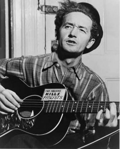 "A black and white photograph of Woody Guthrie playing a guitar with the words ""this machine kills fascists"" written on it"