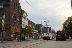A color photograph of a streetcar passing by shops in Media, Pa.
