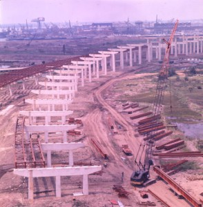 A color photograph of construction of I-95, showing pylons in place and cranes preparing to lift the road deck.