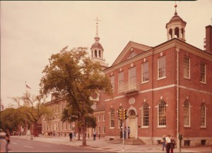 color photograph of independence hall, taken from across the street, caddy-corner to the building. a tree stands outside the entrace and a few people populate the street