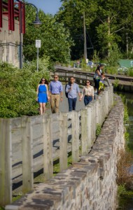 People enjoying a walk on the Manayunk Canal Towpath, now a modern day park.