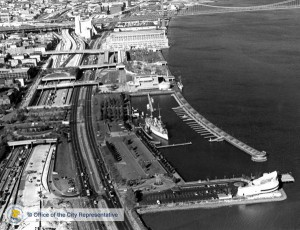Black & white aerial photo of Penn's Landing waterfront, showing the harbor at Spruce Street, with USS Olympia at pier.