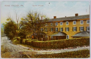Scan of a postcard, in color. The valley rose guesthouse is photographed from an angle. The building is bright yellow with two rows of small white windows. The building is surrounded by a short hedge and obscured by a few trees. The road wraps around the building in the lower half of the postcard.