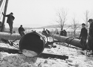 Workers with a portion of pipe for the War Emergency Pipeline.