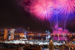 A photograph of Penn's Landing at night time. The winter festival, Winterfest, is taking place and the ice skating rink with many skaters is visible in the forground of the picture. Above, the Ben Franklin Bridge, Delaware River, and neighboring Camden are illuminated by pink and purple fireworks