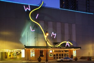 A color photograph of the Wilma Theatre at night, showing the neon facade