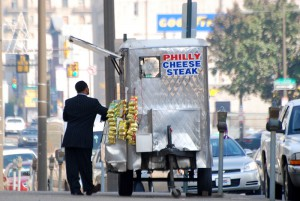 Man in suit awaiting lunch from a cheesesteak vendor on North Broad Street in 2008.