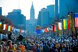 Photograph taken from the middle of the Benjamin Franklin Parkway, looking towards City Hall, which is in the distance. A large crowd covers the street and a colorful Madeiline balloon floats over the crowd. Colorful flags for various countries line the parkway on either side, elevated above the crowd.