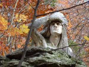 color photo of Lenape chieftan's face with right arm raised to shade eyes while scouting the distance. topmost part of statue in Wissahickon Valley Park.