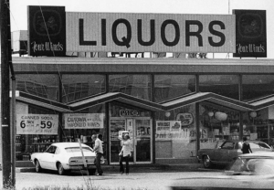 a black and white photograph of the Four Winds liquor store on Admiral Wilson Boulevard