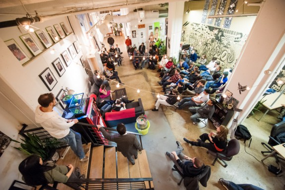 color photograph of large space at Indy Hall co-working with about three dozen people gathered in informal meeting.
