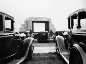 a black and white photograph of automobiles parked in front of the drive-in movie screen in Camden