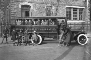 A black and white photo depicting children with disabilities boarding a school bus in 1923.