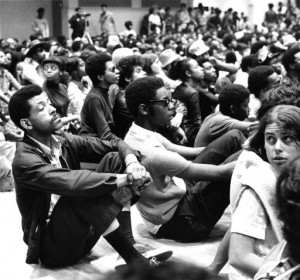 A black and white photograph of a seated crowd at the Black Panther Party convention, Temple University