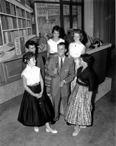 a black and white photograph of Dick Clark on the set of American Bandstand with five teenage guests