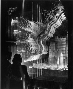 black and white photo with two silhouettes in left foreground looking at an exhibit using transparent maps of the city to illustrate the city's growth from 1782 to 1947.