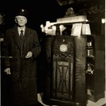 Black and white photograph of an older gentleman standing next to a large RCA Victor radio.