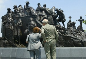 Color photograph of the Irish Memorial statue. The statue is about thirty feet wide and has many figures carved in to its bronze surface. An older couple, a man and woman, are looking at the statue with their backs to the camera.