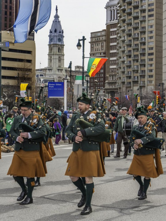 Color photograph of a group of men playing bagpipes. They are wearing kilts and other traditional Irish clothing. Behind them city hall and a large crowd of spectators is visible.