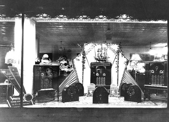 Black and white photo depicting a department store window display with several different models of Philco radios.