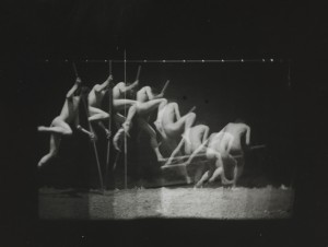 a black and white time-lapse image of a nude male pole-vaulting.  It captures the figure at timed intervals, resulting in about eight apparent semi-transparent overlapping figures going through the singular motion of pole-vaulting.