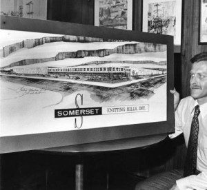 The president of the Somerset Knitting Mills is shown here looking over the architectural rendering of the new building in 1976