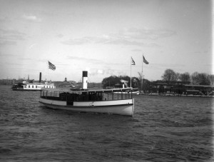 A photograph of a tugboat, with a dock for Ridgway Park in the background.