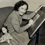 A photograph of Marjorie Buell working on an illustration while sitting at her drawing table. A