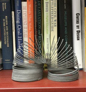 An image of a slinky in the foreground with books on a bookshelf in the background.