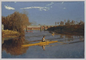A landscape painting of a river, reflecting a close embankment to the left side and a more distant one on the right.  Two bridges run parallel with the horizon line, and the main subject of the painting is Max Schmitt, seating in a single, yellow scull, turned to his right to look at the viewer.  Another sculler is rowing away toward the bridges and horizon behind him.