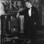 Black and white photo depicting a man standing next to an Atwater Kent radio.