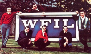 "Color photograph depicting six of the Famous 56 ""Boss Jocks"" posed around a WFIL sign."