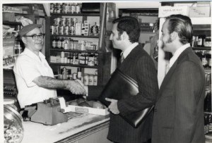 A black and white photograph of two men in business suits shaking hands with a merchant inside of a store