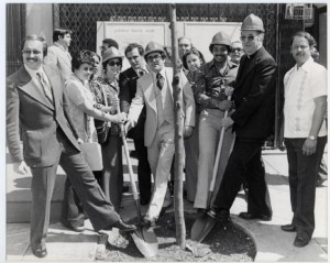 A black and white photograph of a group of people posing with a newly-planted tree and shovels